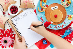 Child writes letter for santa, wish list to Christmas on table w. Ith gifts and reindeer pancake Royalty Free Stock Photography