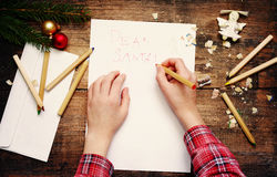 Child writes the letter to Santa Claus. Child`s hands, the sheet of paper, pencils and Christmas decorations Stock Photography