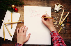 Child writes the letter to Santa Claus. Child`s hands, the sheet of paper, pencils and Christmas decorations Royalty Free Stock Photos