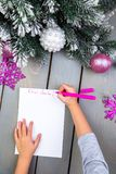 Child writes the letter to Santa Claus. Kid hands. Top view. Royalty Free Stock Images