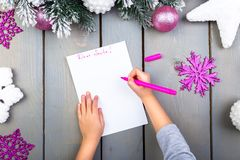 Child writes the letter to Santa Claus. Kid hands. Top view. Royalty Free Stock Photography