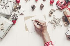 Child writes letter to Santa Claus top view. kid hands holding p. Encil and making wish list and paper with christmas decorations and ornaments and presents on Royalty Free Stock Images