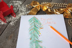 Child writes letter to Santa and draw a Christmas tree. Royalty Free Stock Images