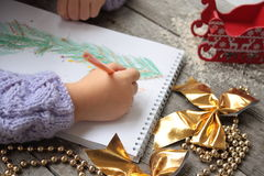 Child writes letter to Santa and draw a Christmas tree. Golden Christmas beads and gold ribbon bows on wooden Stock Image
