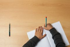 Child writes on a notebook. Royalty Free Stock Image
