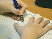 Child writes in a notebook close-up stock image