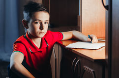 Child writes in a notebook. The child late at night writing in a notebook, doing homework,set goals Stock Photography