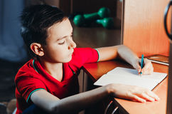 Child writes in a notebook. The child late at night writing in a notebook, doing homework,set goals Stock Image
