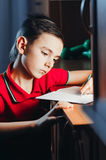Child writes in a notebook. The child late at night writing in a notebook, doing homework,set goals Royalty Free Stock Photography