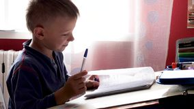 Child writes with a pen in a notebook. 2019 stock footage