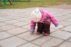 Child writes on road Royalty Free Stock Photo