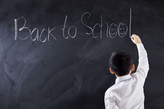Child writes text Back to School in class Royalty Free Stock Images