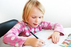 Child writing. A blonde girl 6 years old teach to writing Stock Photos