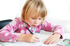 Child writing. A blonde girl 6 years old teach to writing Stock Image