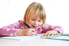 Child writing. A blonde girl 6 y.o. teach to writing Stock Image