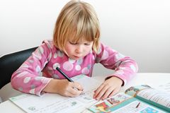 Child writing. A blonde girl 6 y. o. teach to writing Stock Photos