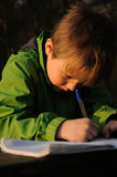 Child writing. Young child in green jacket writing to notebook Stock Photo