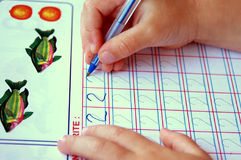 Child writing. Hands of a toddler child writing down numbers with a pen in a book Royalty Free Stock Images
