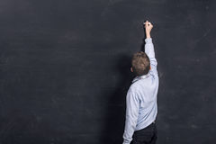 Child writing on black chalkboard Royalty Free Stock Photo