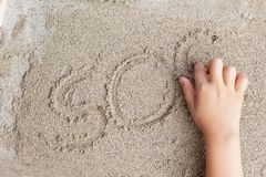 A child is writing a finger on the sand of the word SOS Stock Photography