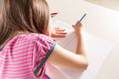 Child writing her homwork at a desk with a blue pencil crayon Stock Image