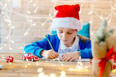 Child writing a letter to Santa Claus at home. Royalty Free Stock Image