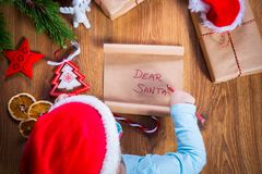 Child writing letter to Santa Claus. Top view of child writing letter to Santa Claus for Christmas Royalty Free Stock Images