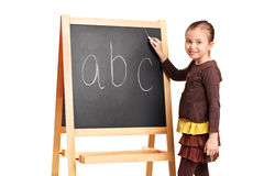A child writing letters on a school board Stock Photo