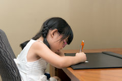 Child writing. Little Asian girl with glasses writing at the table Stock Images
