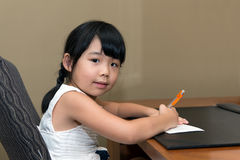 Child writing. Little Asian girl is writing at the table Stock Photos