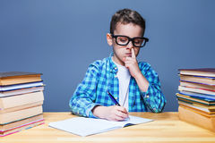 Child writing in notebook and picks his nose Royalty Free Stock Photography
