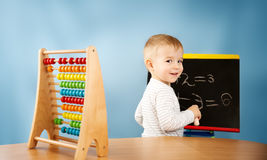 Child writing numbers on chalkboard Royalty Free Stock Photos