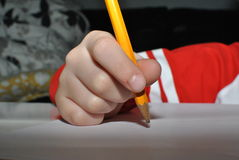 Child writing with pencil stock image