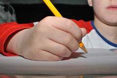 Child writing with pencil. Small hand writing with pencil royalty free stock image