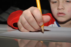 Child writing with pencil. Small hand writing with pencil royalty free stock photography