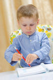 Child writing with a red pencil Stock Photo