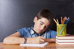 Child writing. In the school table Royalty Free Stock Images