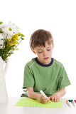 Child writing thank you note. A 6 year old boy writing a thank you sign with markers isolated on white Royalty Free Stock Photography