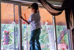 Child writing on window with glass markers. Child decorates a window for halloween, with colorful window markers Stock Images