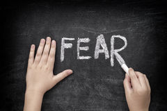Child writing word Fear on blackboard Royalty Free Stock Images
