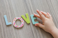 Child is Writing Word Love From Colorful Toy Letters Royalty Free Stock Images