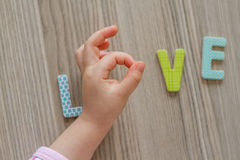 Child is Writing Word Love From Colorful Toy Letters Stock Photos