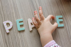 Child is Writing Word Peace From Colourful Toy Letters Royalty Free Stock Photography