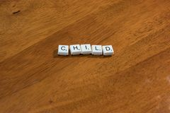 Child written in game pieces. On wood background Royalty Free Stock Images