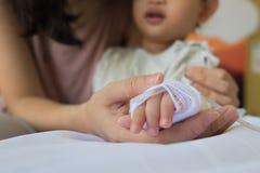 Child& x27 della tenuta della madre; mano di s che riceve la soluzione salina del dispositivo di venipunzione nel hosp Fotografie Stock Libere da Diritti