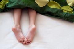 Child& x27; s-Füße unter Decke Stockfotos