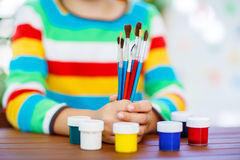 Child& x27;s hands with lots of brushes and colorful watercolors Stock Images