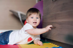 The child 1 year old opens the drawers or closet . Happy baby boy lies on floor at children`s room and playing. royalty free stock images