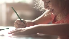 Child of 6 years draws houses sitting at a table. little girl in the morning sun. Children draw with pencils at home sitting at a table. two little girls sister stock video footage