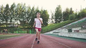 The child of 8 years is engaged in sports in stadium. the little girl is running along the path in the stadium. slow